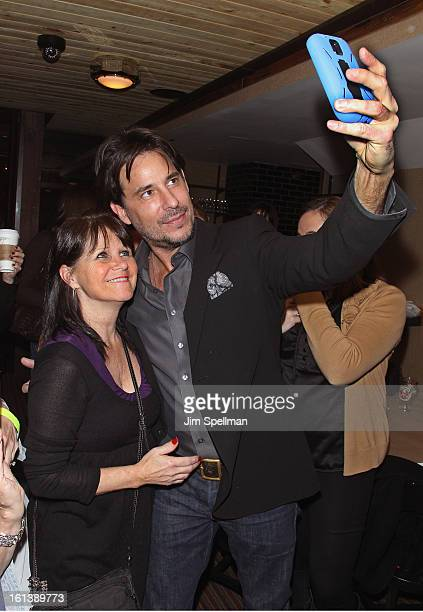 Actor Ricky Paull Goldin with a fan attend the Spontaneous Construction premiere at Guys American Kitchen Bar on February 10 2013 in New York City