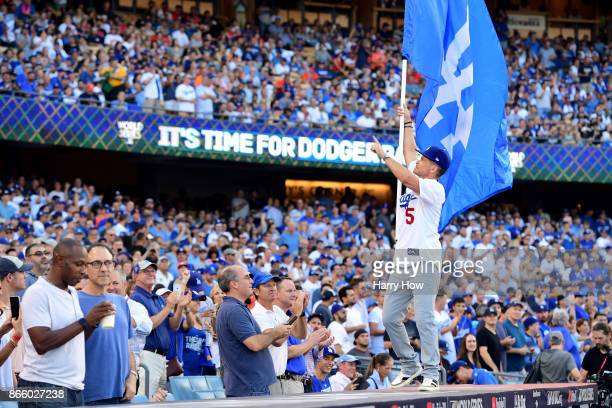 Actor Rob Lowe waves a Los Angeles Dodgers flag before game one of the 2017 World Series between the Houston Astros and the Los Angeles Dodgers at...