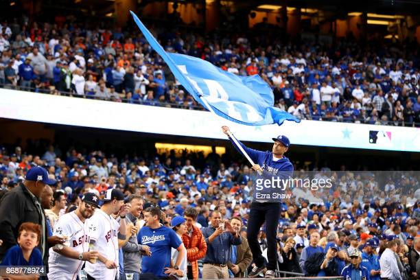 Actor Rob Lowe waves a Los Angeles Dodgers flag before game six of the 2017 World Series between the Houston Astros and the Los Angeles Dodgers at...