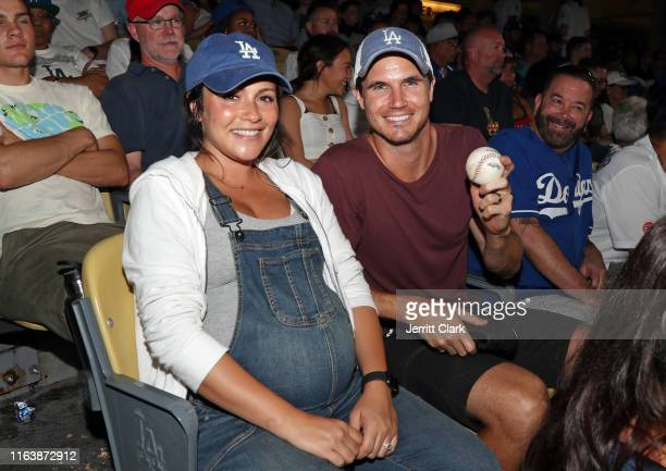 Actor Robbie Amell poses for a photo with wife Italia Ricci and a foul ball he caught at the Los Angeles Dodgers Game at Dodger Stadium on July 23...