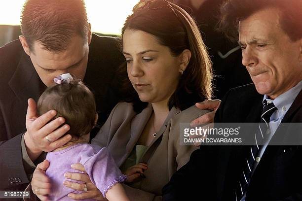 Actor Robert Blake grimaces as his daugther Delina Blake holds his 11monthold daughter Rose Lenore Sophie Blake as they arrive at the grave site of...