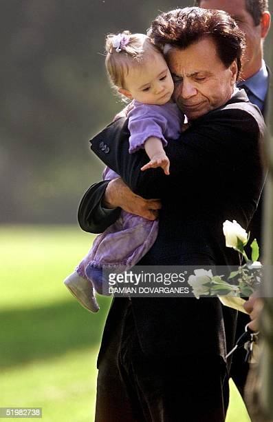 Actor Robert Blake hugs his 11monthold daugther Rose Lenore Sophie Blake as she leans down to grab a white rose picked from the coffin bearing her...
