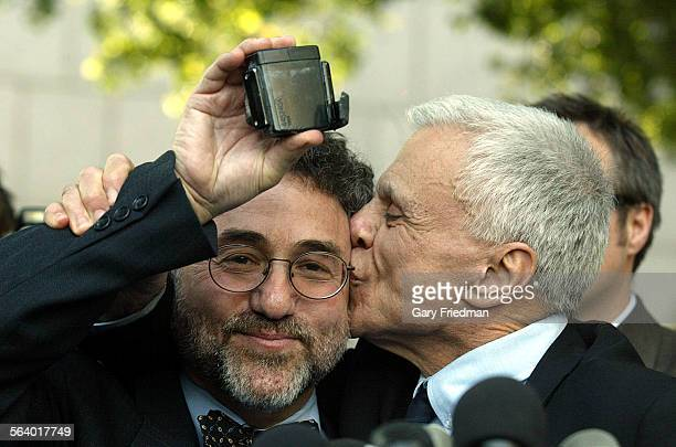 Actor Robert Blake kisses his attorney Gerald Schwartzbach after Blake cut off his court monitor from his ankle at a press conference outside...