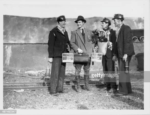 Actor Robert Donat chatting to extras during the filming of 'The Citadel' at Denham Studios June 24th 1938