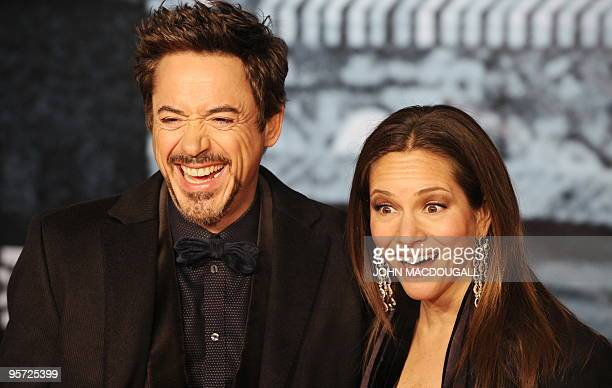 Actor Robert Downey Jr and his wife producer Susan Downey share a laugh as they pose for photographers on the red carpet prior to the German premiere...