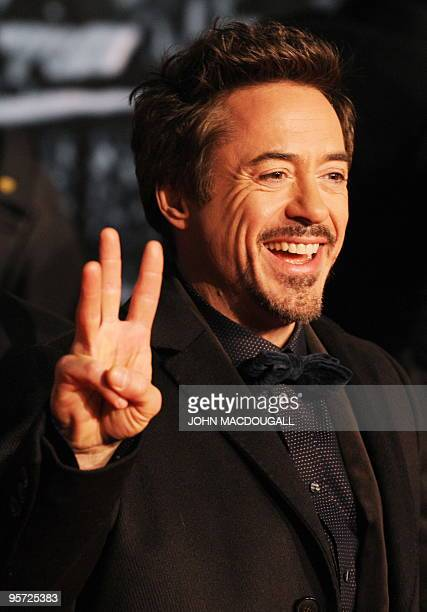 Actor Robert Downey Jr flashes a three-fingered sign as he poses for photographers on the red carpet prior to the German premiere of the film...