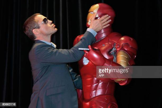 Actor Robert Downey Jr holds an 'Iron Man' mannequin at the premiere of his new film in Sydney on April 14, 2008. The American actor is in Australia...