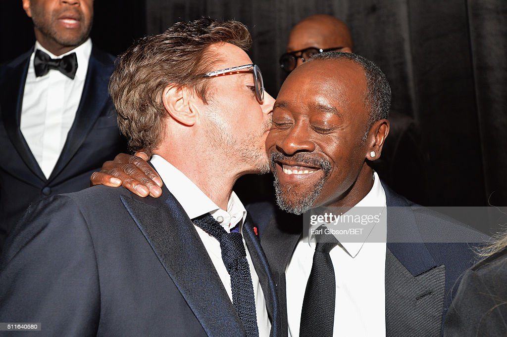 Actor Robert Downey Jr. (L) kisses honoree Don Cheadle during the 2016 ABFF Awards: A Celebration Of Hollywood at The Beverly Hilton Hotel on February 21, 2016 in Beverly Hills, California.