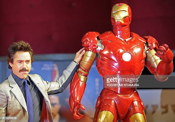 Actor Robert Downey Jr. Poses by a life-size Iron Man model during a press conference on his latest movie Iron Man, in Tokyo, on September 3, 2008....