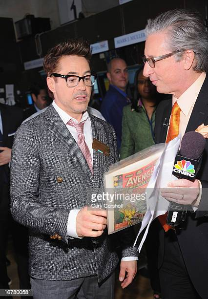 Actor Robert Downey Jr seen being shown an Iron Man first edition copy by Bob Pisani of CNBC at the New York Stock Exchange on April 30 2013 in New...