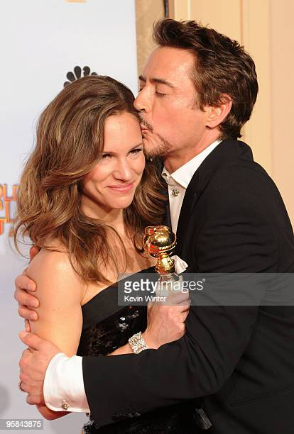 """Actor Robert Downey Jr., winner of the Best Actor in a Motion Picture Comedy or Drama for """"Sherlock Holmes"""" kisses his wife Susan Downey as they pose..."""