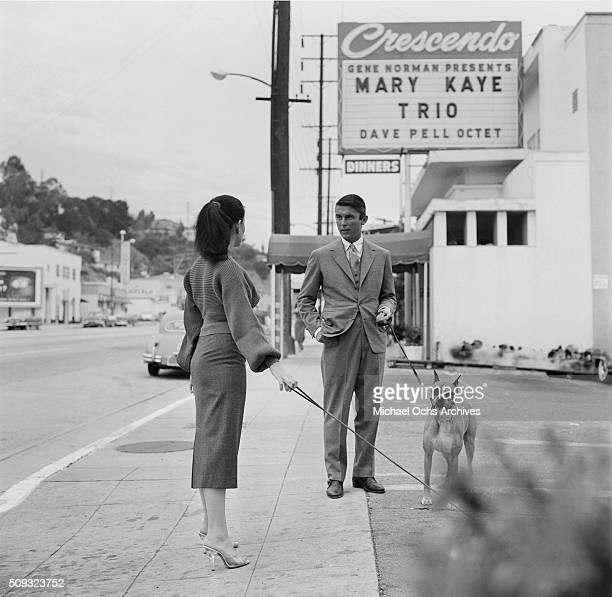 Actor Robert Evans with his boxer dog talks with actress Joan Bradshaw outside the Crescendo in Los AngelesCalifornia