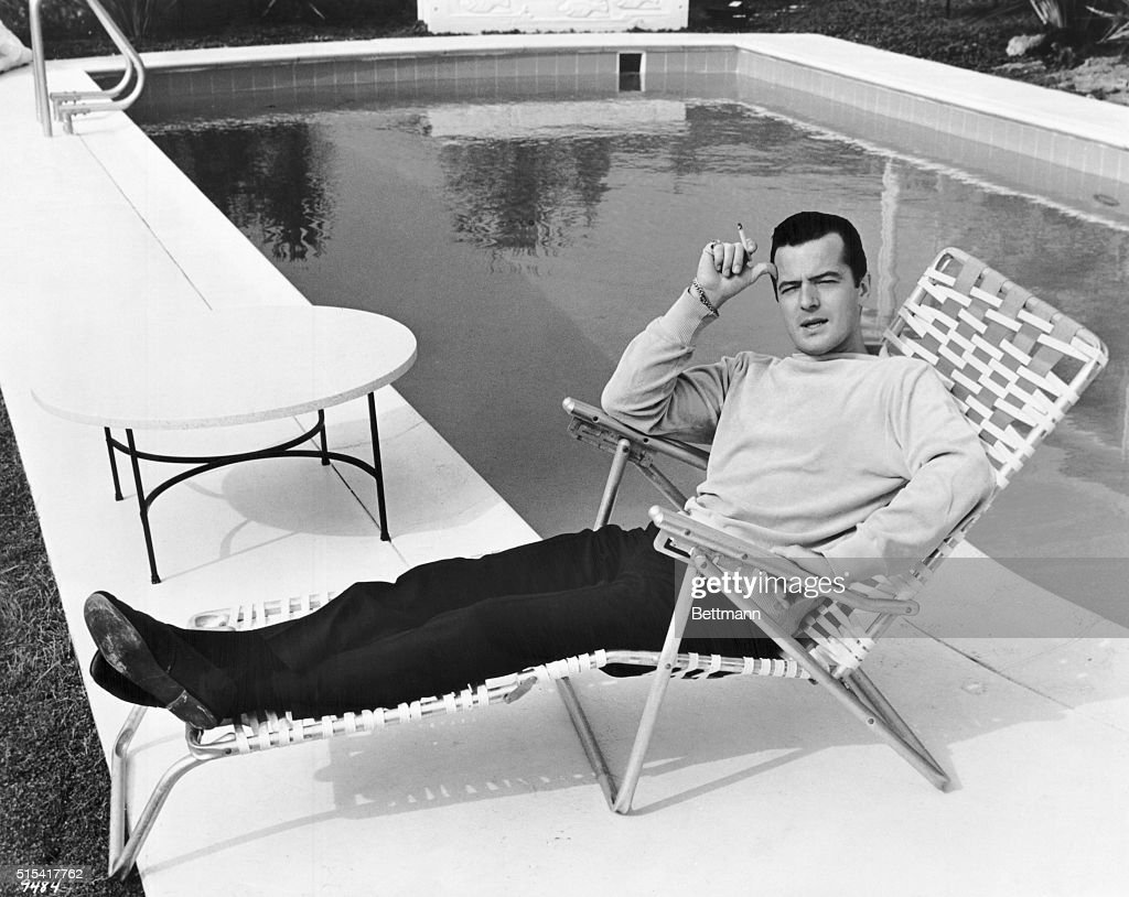 Actor Robert Goulet relaxing by a swimming pool in a promotional portrait for the 1964 comedy film Honeymoon Hotel.