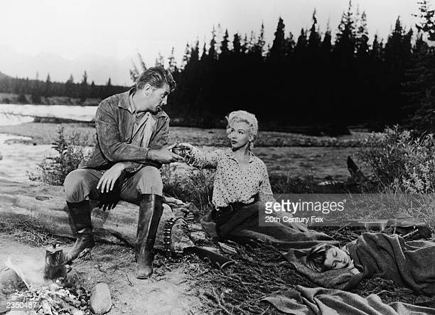 Actor Robert Mitchum accepts a cup from Marilyn Monroe as they sit by a riverbank campfire in a still from the film 'River Of No Return' directed by...