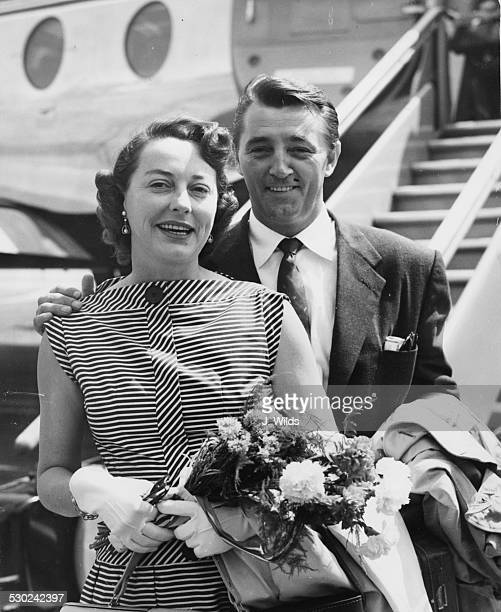 Actor Robert Mitchum and his wife smiling as they arrive at London Airport July 27th 1955