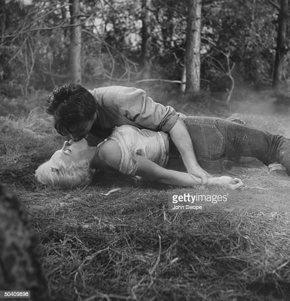 Actor Robert Mitchum kissing Marilyn Monroe as he wrestles with her on the ground in scene from film River of No Return