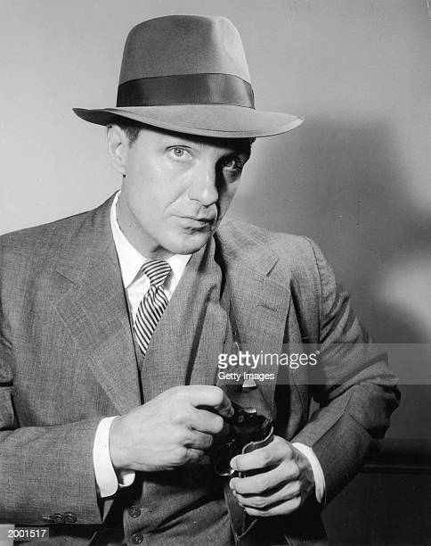 Actor Robert Stack in costume as Eliot Ness holds a gun tucked in a shoulder holster in a 1959 promotional portrait for the television series The...