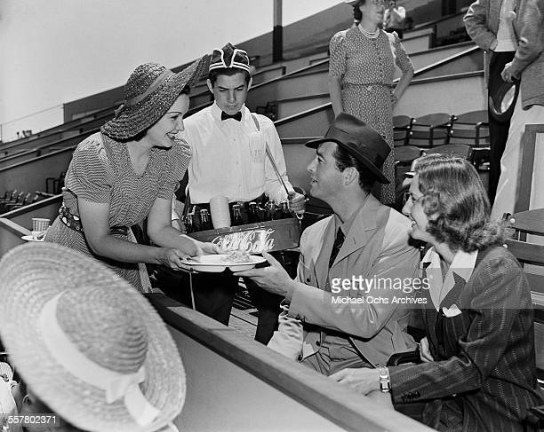 Actor Robert Taylor and his wife actress Barbara Stanwyck attend a game as they are offered food and a CocaCola in Los Angeles California