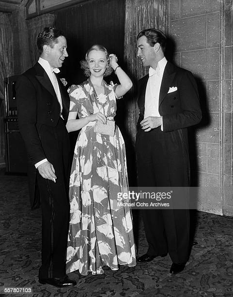 Actor Robert Taylor poses with actress Virginia Bruce and her husband screen writer J Walter Ruben at an event in Los Angeles California