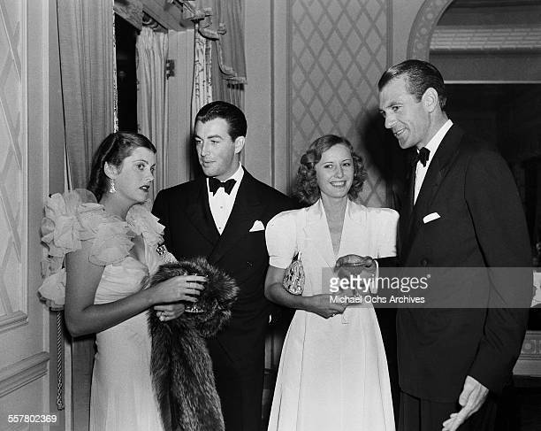 Actor Robert Taylor talks with Veronica Cooper as actress Barbara Stanwyck talks with actor Gary Cooper during an event in Los Angeles California