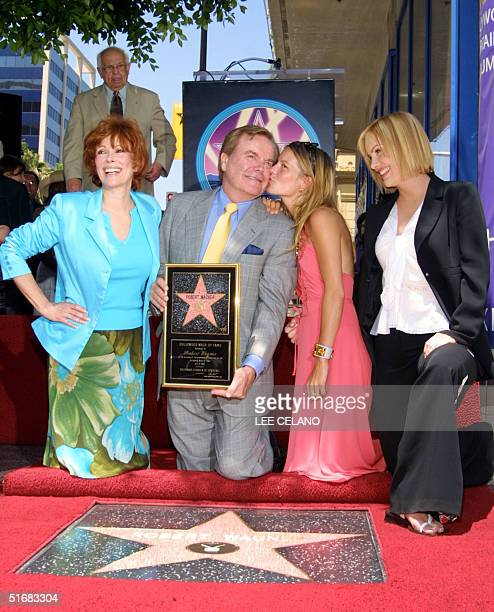 Actor Robert Wagner gets a kiss from daughter Courtney and wife actress Jill St John and daughter Katie look on during an unveiling ceremony for his...
