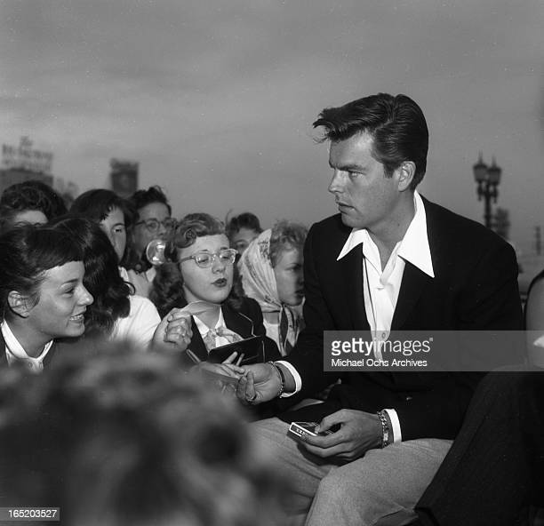 Actor Robert Wagner signs autographs for fans out of a convertible car on April 21 1957 in Los Angeles California