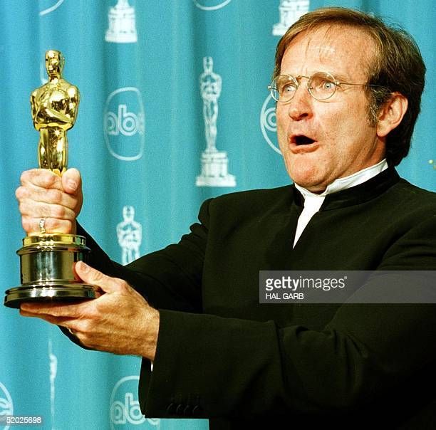 "Actor Robin Williams holds the Oscar he won for Best Supporting Actor for his role in ""Good Will Hunting"" during the 70th Annual Academy Awards 23..."