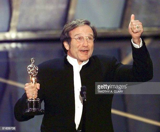Actor Robin Williams holds up his Oscar after winning in the Best Actor in a Supporting Role category during the 70th Academy Awards 23 March at the...