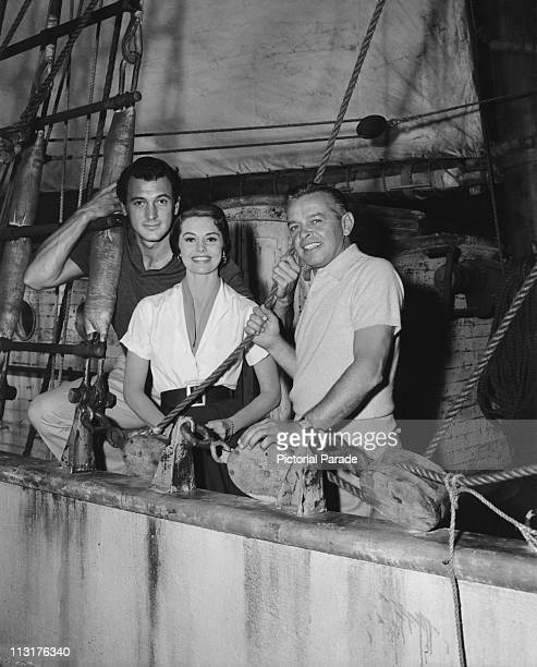 Actor Rock Hudson actress Cyd Charisse and director Joseph Pevney on board a boat during the filming of 'Twilight For The Gods' in 1958