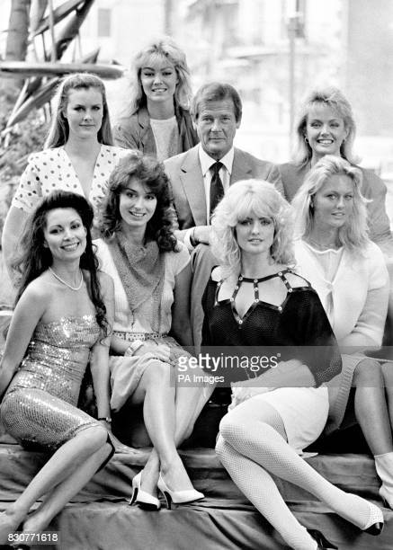 Actor Roger Moore alias 007 James Bond in London with seven of the girls who will appear in the new Bond film Octopussy At back left to right Carolyn...