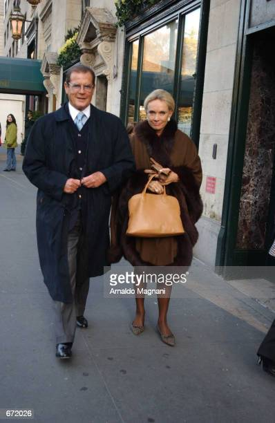 Actor Roger Moore walks with his fiance Kristina Tholstrup on Fifth Avenue November 18, 2001 after eating at Cipriani's Restaurant in New York City.