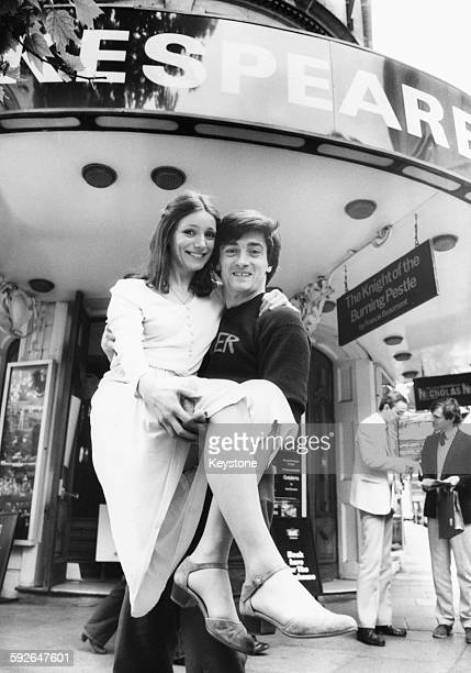 Actor Roger Rees lifting up actress Emily Richards in his arms outside the Aldwych Theatre promoting their Royal Shakespeare production of 'The Life...