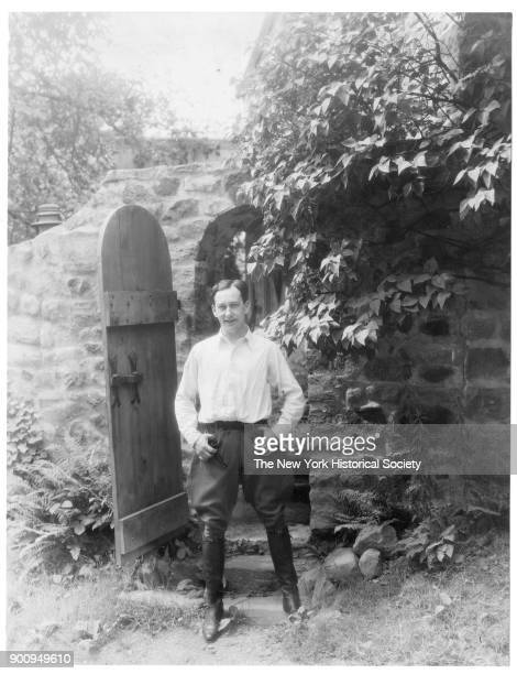 Actor Rollo Peters in white shirt and breeches holding pipe standing with legs shoulderwidth apart in front of a wooden door in a stone wall 1922