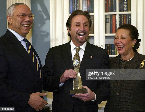 US actor Ron Silver stands with his award beide US Secretary of State Colin Powell and Mrs Alma Powell during ceremonies honoring the service of...