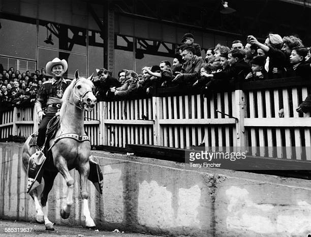 Actor Roy Rogers the 'King of Cowboys' riding his horse Trigger in front of a group of school children at Harringay Stadium London March 20th 1954
