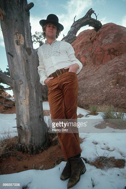 Actor Ryan O'Neal wears a Westernstyle outfit and leans against a tree while on location for the motion picture Wild Rovers
