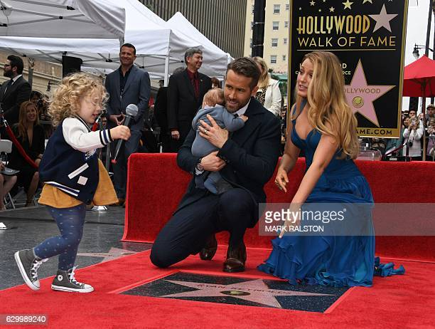 Actor Ryan Reynolds holds his unnamed new baby as his wife Blake Lively and daughter James look on during the Deadpool actors Hollywood Walk of Fame...