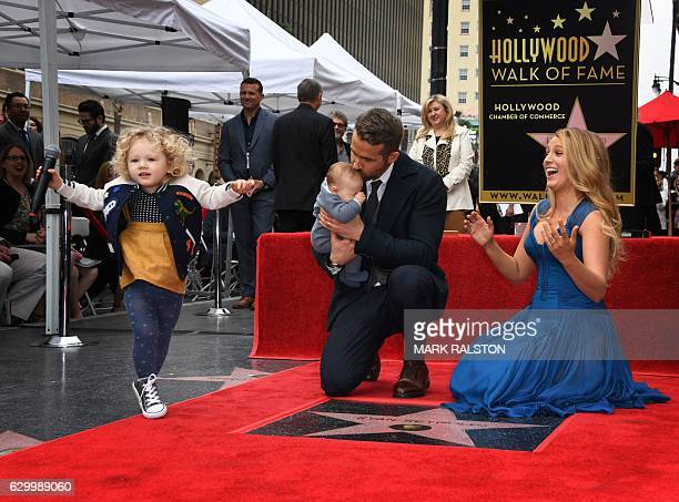 Actor Ryan Reynolds kisses his unnamed new baby as his wife Blake Lively and daughter James look on during the Deadpool actors Hollywood Walk of Fame...