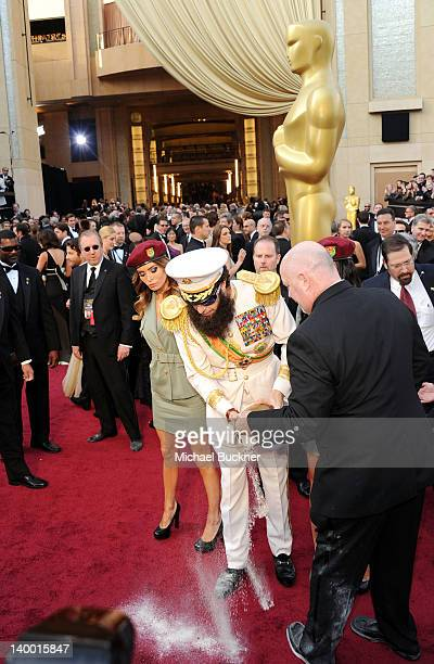 Actor Sacha Baron Cohen dressed as his character 'General Aladeen' from 'The Dictator' spills Kim Jong Il's ashes on the red carpet as he arrives at...