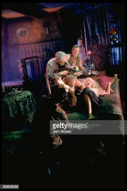 Actor Salmi watching Cobb bite leg of woman tied to bed as musicians play in scene fr film The Brothers Karamazov based on novel by Dostoevsky