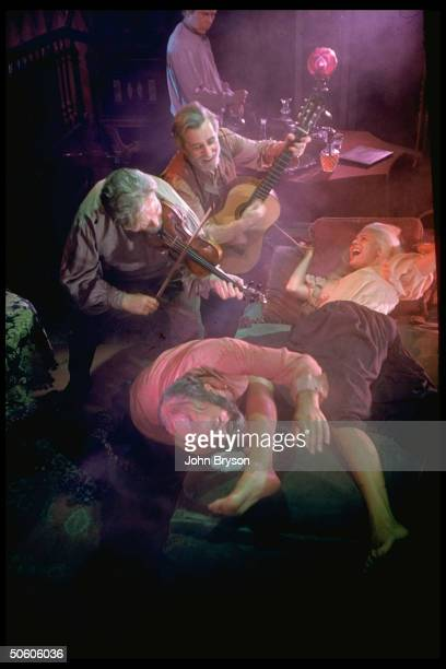 Actor Salmi watching Cobb tickle feet of woman tied to bed as musicians play in scene fr film The Brothers Karamazov based on novel by Dostoevsky