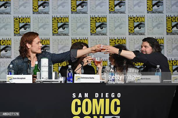 """Actor Sam Heughan and writer/producer Ronald D. Moore share a toast onstage at the Starz: """"Outlander"""" panel during Comic-Con International 2015 at..."""