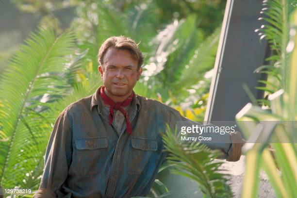 Actor Sam Neill as Dr Alan Grant standing next to an electric fence in a scene from the film 'Jurassic Park' 1993