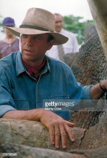 Actor Sam Neill as Dr. Alan Grant, tending to a sick Triceratops in a scene from the film 'Jurassic Park', 1993.