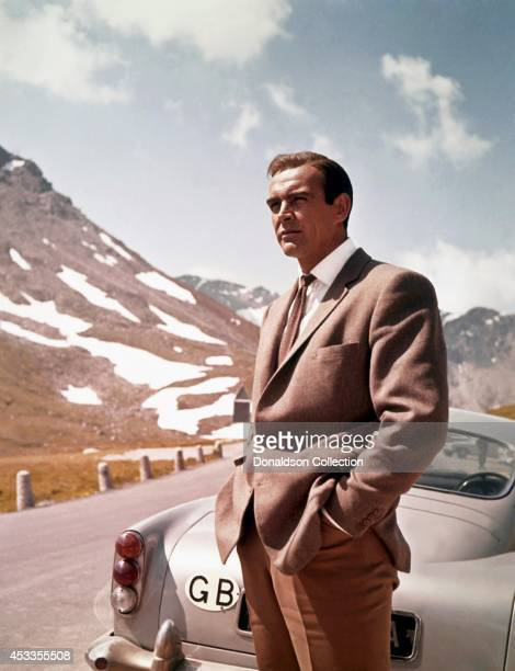 Actor Sean Connery poses as James Bond next to his Aston Martin DB5 in a scene from the United Artists film 'Goldfinger' in 1964