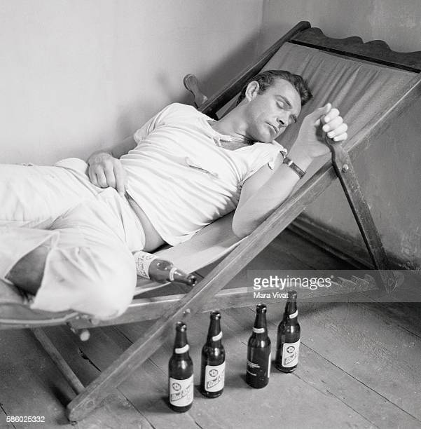 Actor Sean Connery sleeps on a lounge chair beside a row of empty Red Stripe beer bottles possibly in character for a movie role Connery played James...
