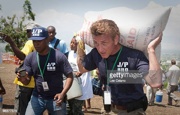 Actor Sean Penn carries belongings of a shelter camp resident as they are prepared to be relocated to a new camp April 10 2010 in Petionville Haiti...