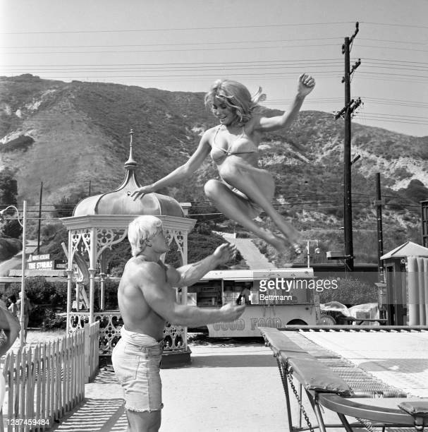 """Actor Sharon Tate bounces off a trampoline into the brawny arms of David Draper, the current """"Mr. America,"""" during a beak in filming of """"Don't Make..."""