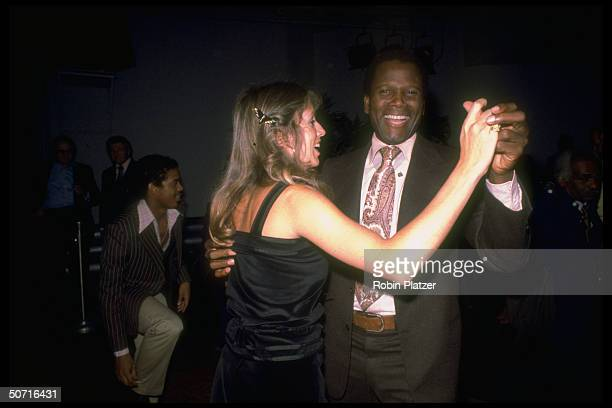 Actor Sidney Poitier dancing with wife Joanna Shimkus at Studio 54.