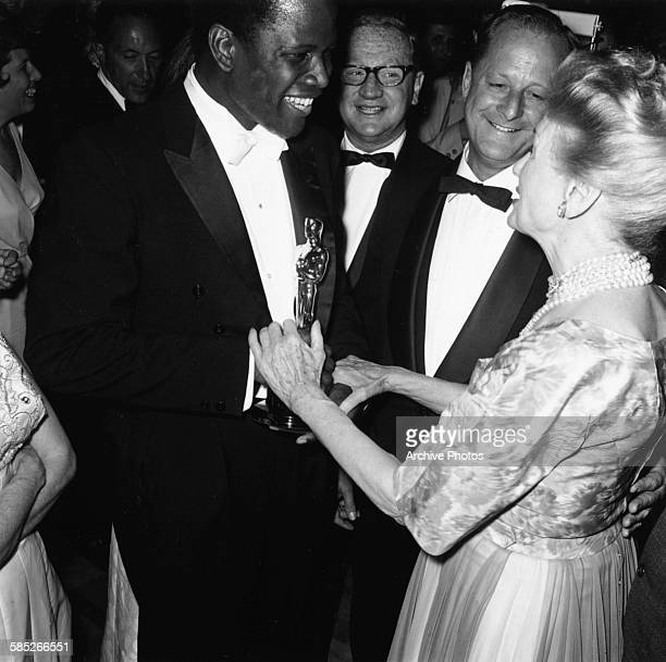 Actor Sidney Poitier holding his Best Supporting Actor for the film 'Lilies of the Field' attending the Governors Ball after the 36th Academy Awards...
